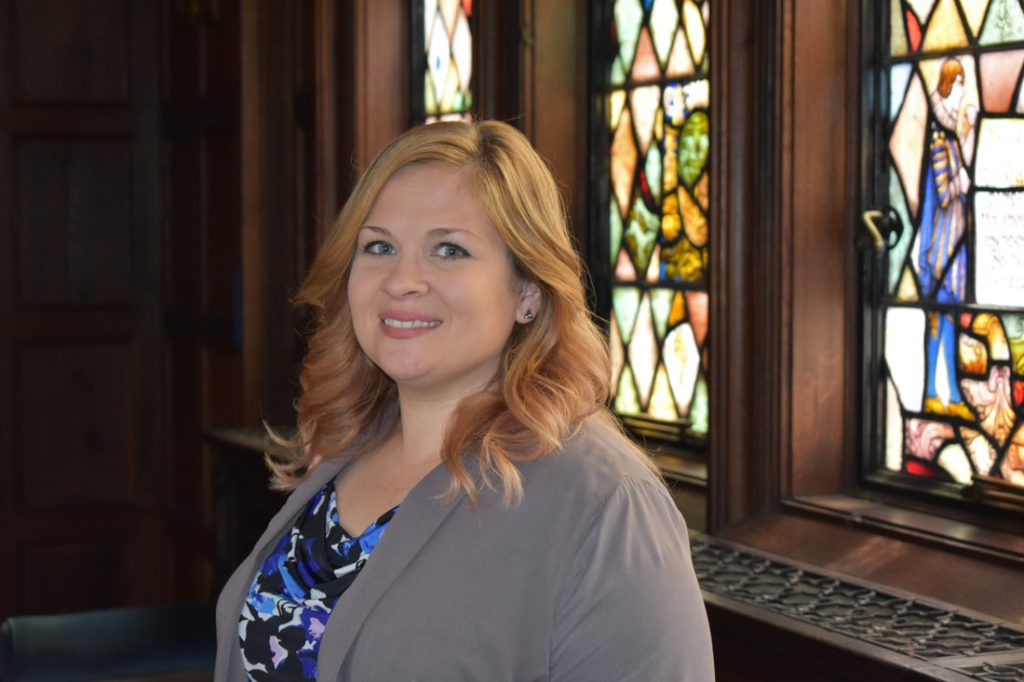 Sarah is standing with a wall and church windows behind her. She has blonde hair, blue eyes, white, and is wearing a gray jacket with blue, navy blue, pink and white patterned shirt