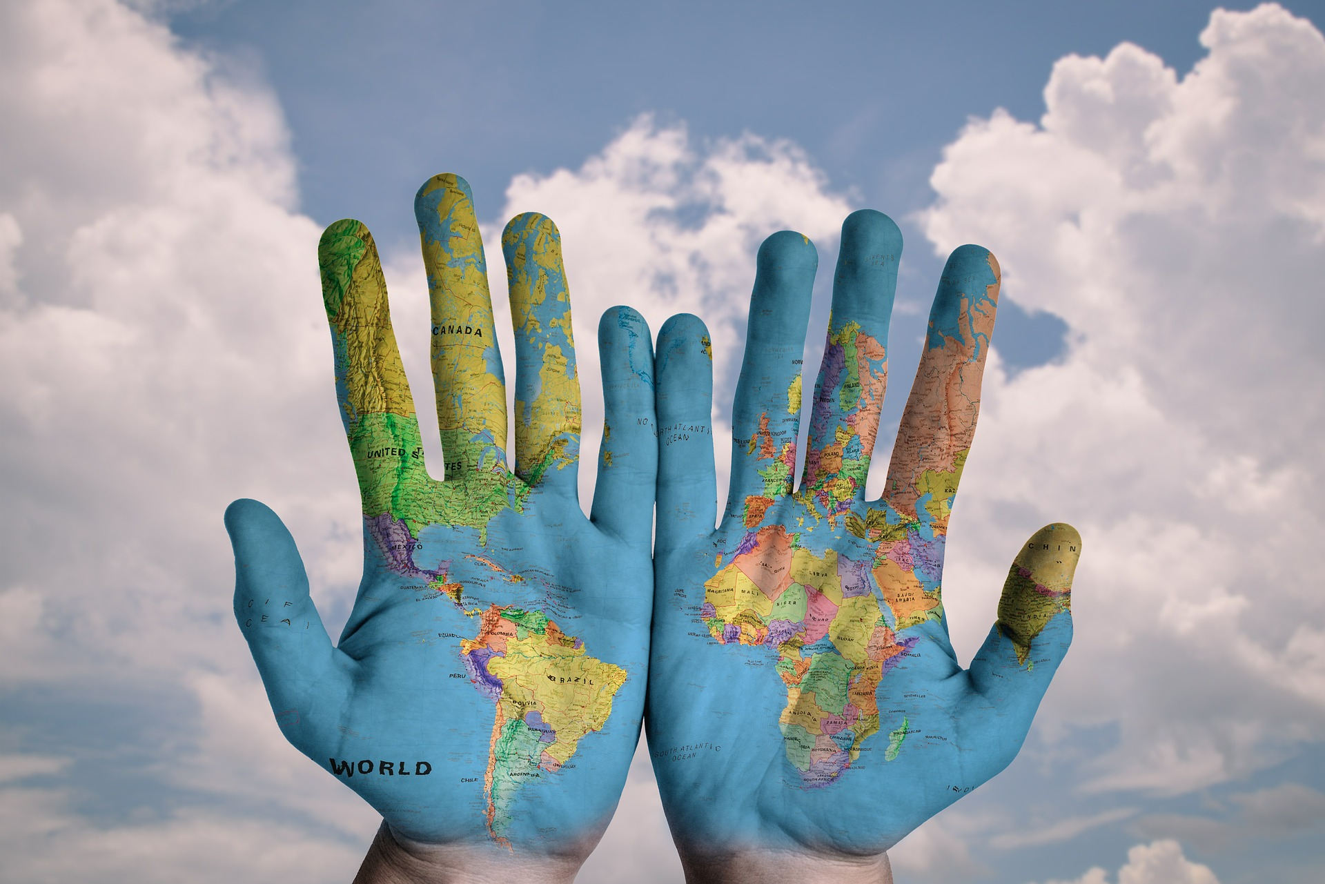 Background with clouds and blue sky, two hands with the world map on them