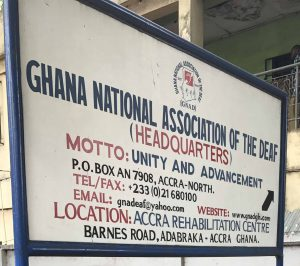 Sign showing Ghana National Association of the Deaf with Sarah standing in front