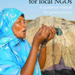 "The image shows the cover of the manual titled ""Capacity Building for Local NGOs: A Guidance Manual for Good Practice"". A woman with a bright blue head covering stands outside, mouth open as if speaking, gesturing with her hands."