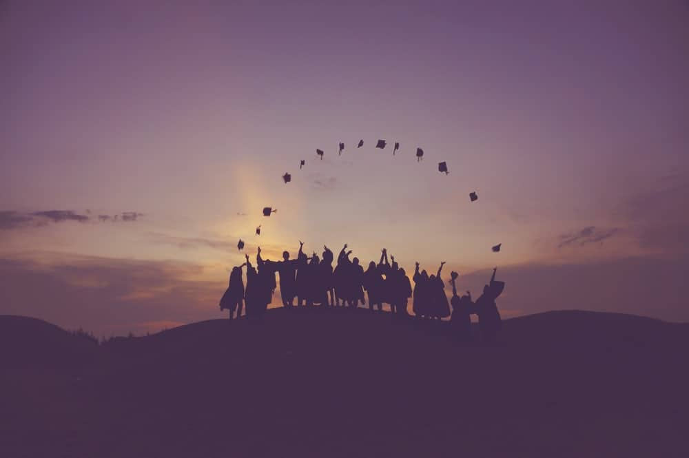 Photo shows graduating students standing in a line throwing their graduation caps into the air at sunset. The caps form an arc in the air before they start to fall.