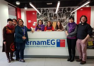 "nzf staff stand in front of a table with a sign ""sernam eg"""
