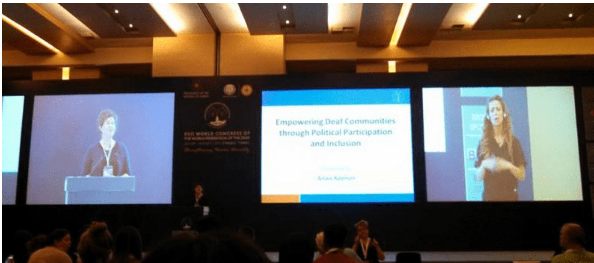 "This photo shows three screens at the front of a conference room. The screen at left shows Anais Keenon presenting. The middle screen shows a power point slide with the presentation title ""Empowering Deaf Communities through Political Participation and Inclusion"". The right screen shows an interpreter."