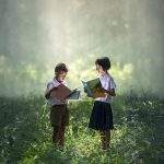 Two children wearing school uniforms stand in a forest while each is reading a book.