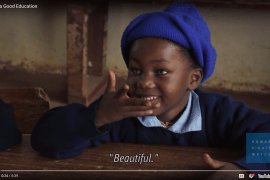 """This screenshot was taken from a video on achieving a good education through sign language. A young girl seated at a school desk smiles at someone off camera. This shot was taken while the girl was signing """"Beautiful"""". At the bottom right is the logo for Human Rights Watch, who produced the video. Below that is the logo and icons typical for a YouTube video."""