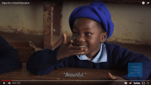 "This screenshot was taken from a video on achieving a good education through sign language. A young girl seated at a school desk smiles at someone off camera. This shot was taken while the girl was signing ""Beautiful"". At the bottom right is the logo for Human Rights Watch, who produced the video. Below that is the logo and icons typical for a YouTube video."