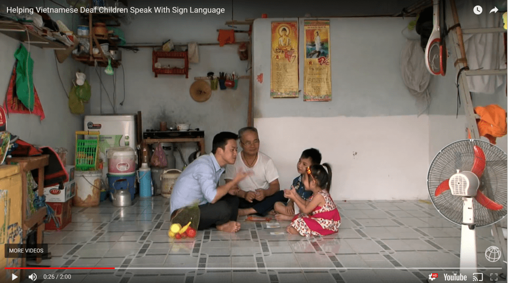 This screenshot is taken from a video about a project teaching sign language to Deaf children and families in Vietnam. In this scene, two men are seated on the floor of a home signing with two young children teaching them sign language. Some sparse furniture, home supplies, and storage are pushed against the walls of the home.