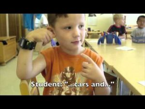 "A young boy is signing to the camera. The subtitle on the screen says ""Student: ""...cars and..."""