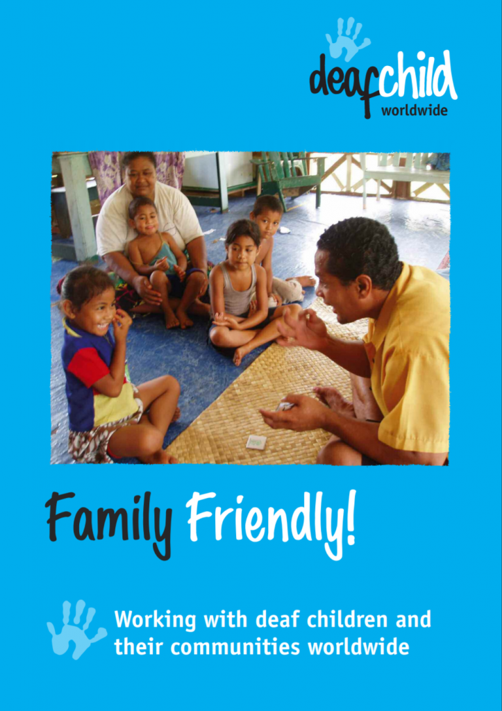 "Cover of ""Family Friendly! Working with deaf children and their communities worldwide"". A photo on the cover shows a deaf adult teaching sign language to a deaf child while other family members watch."