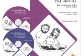 """Screenshot shows the cover of a book, and two accompanying DVDs, entitled """"La familia en tus manos"""". On the cover, a simple black and white line drawing shows a mother and father laying a baby down to sleep."""