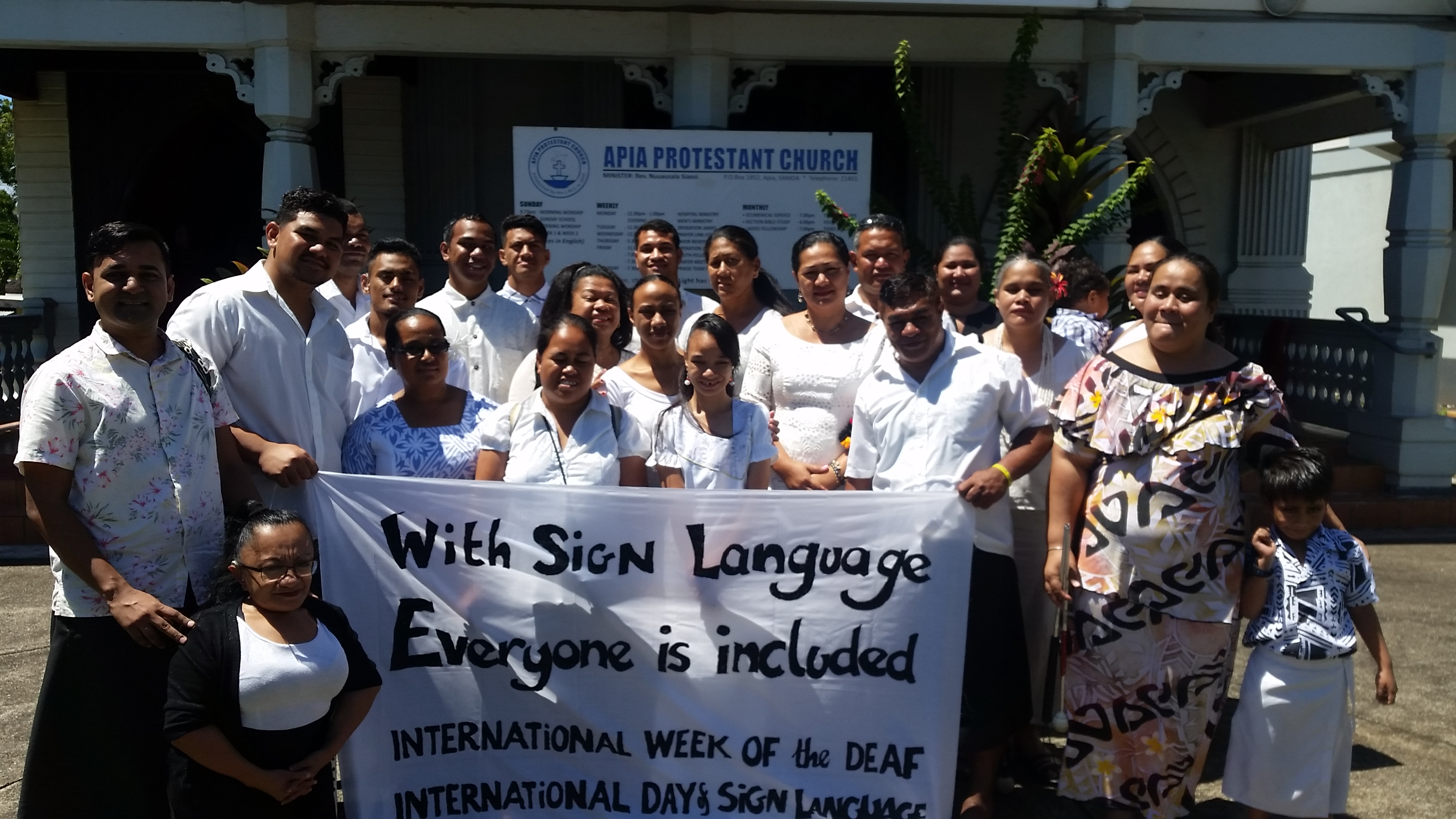 "a group of men and women holding up a sign ""With Sign Language Everyone is Included"""