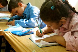 Photo of three young students seated next to each other at the Deaf Unit in Cairo, Egypt. All are writing on paper.