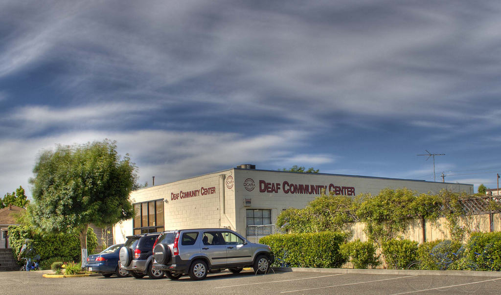 """The corner of a large two-floor building shows lettering on two sides that both say """"Deaf Community Center"""". A few cars are parked in front. No people are in sight."""