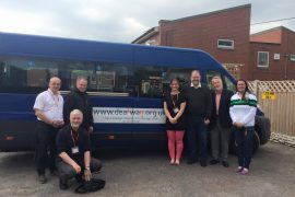 Seven people stand or crouch near a blue van. The van has the web address for www.deafway.org.uk on the side.