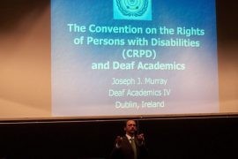 """A man is signing to an audience off camera. Above him is a large projector screen with a power point slide that says """"The Convention on the rights of Persons with Disabilities (CRPD) and Deaf Academics; Joseph J. Murray; Deaf Academics IV; Dublin, Ireland."""