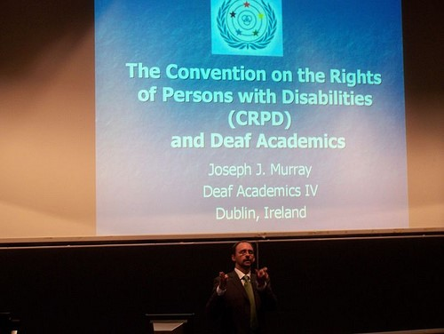 "A man is signing to an audience off camera. Above him is a large projector screen with a power point slide that says ""The Convention on the rights of Persons with Disabilities (CRPD) and Deaf Academics; Joseph J. Murray; Deaf Academics IV; Dublin, Ireland."