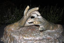"""Photo shows a statue of two hands, each making a loop with the index finger and thumb and interconnecting the loops to make the ASL sign for """"connect"""" or """"connection"""""""