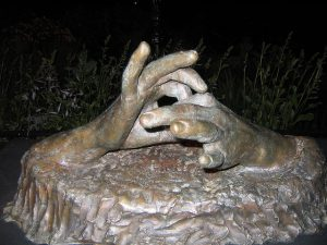 "Photo shows a statue of two hands, each making a loop with the index finger and thumb and interconnecting the loops to make the ASL sign for ""connect"" or ""connection"""