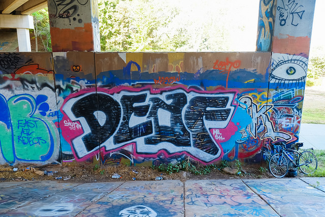 """Large mural with the word """"DEAF"""" spray painted in large letters. A large eye is drawn above the right side of the word."""