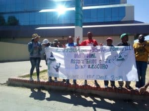 """a group of deaf people standing and holding up a sign saying """"National Association of the Deaf Lesotho"""""""