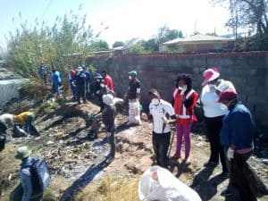Group of deaf people standing along a path and collecting trash