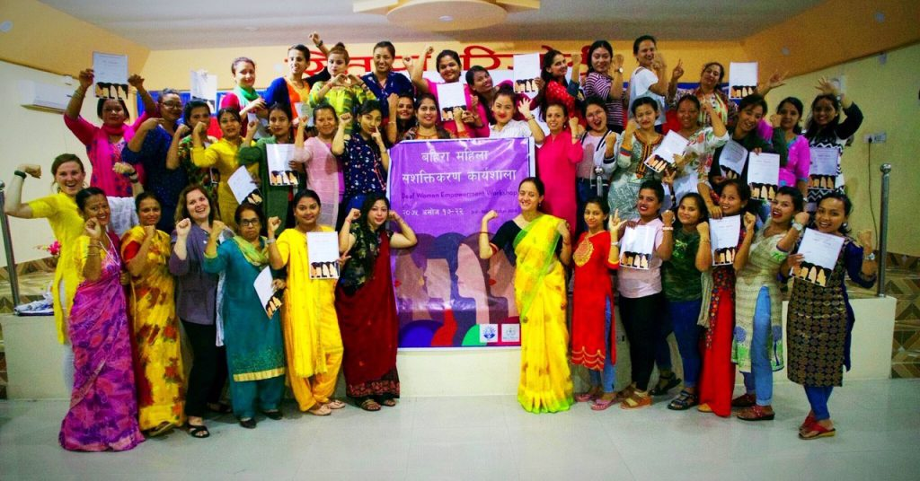 A group of approximately 30 women stand in rows, posing with a large poster in Nepali.