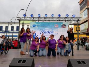 Eight women stand or kneel in front of an International Day of Sign Languages poster on a large open stage outside. The women are signing.
