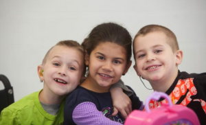 Three young children smile at the camera. At least two are clearly wearing hearing aids.