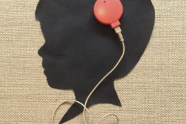 Photo of a cut-out silhouette of a young child's head with the external component of a cochlear implant attached to the skull.