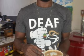 "A man holding a mug of coffee looks at the camera. His T-shirt says ""Deaf"" and has the image of a pair of hands signing ""coffee"" on it."