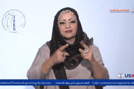 A screen shot of a video in which a woman is signing to the camera. The logo for the International Foundation for Electoral Systems, and the logo for the U.S. Agency for International Development, are on the screen. At the bottom is text in English and Arabic.