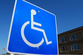 Blue street sign with a wheelchair icon on it.