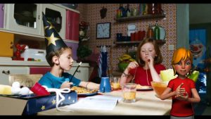 Screenshot taken from a video. In the video, two children are sitting at a kitchen table. At the front of the video, an avatar in the lower right corner shows an animated image of a person who can sign.