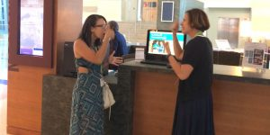 Photo of two women signing to each other at the front desk in a hotel.