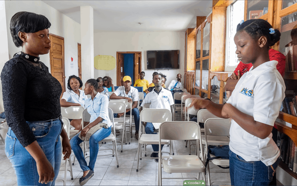 Photo shows adults seated in rows in a classroom. A teacher teaches sign language to young Haiti professionals.