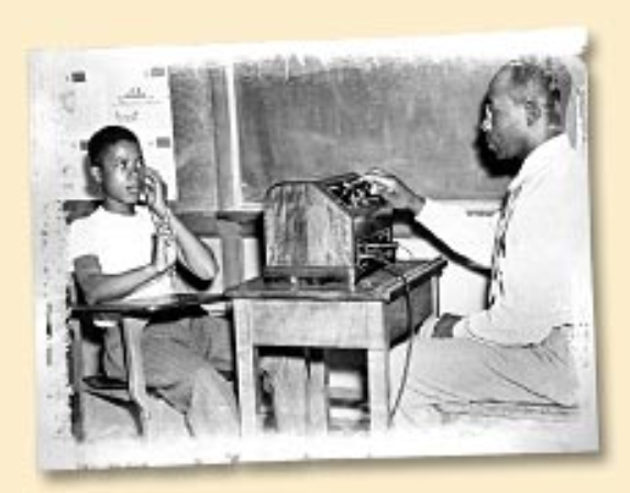 Old black and white photo shows student seated in front of a teacher. A machine is on a desk in between them. A chalkboard is on the wall beside them.