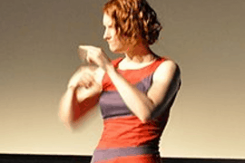 Photo shows a woman signing to someone off camera.