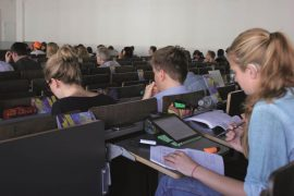 Photo shows university students seated in rows. One young woman with a hearing aid has a tablet at her desk that uses assistive technology to help her understand the lecture. In Germany.