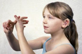 Photo shows a young girl with a hearing aid who is signing.