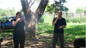 A man and a woman are standing next to each other in front of a tree. Both are signing toward an audience who is off camera.