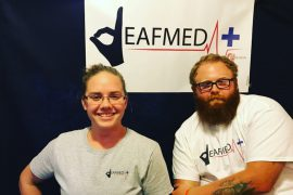 """A woman and a man are looking at the camera. On the wall behind them is a sign that has a logo for DeafMed. The """"D"""" is replaced with a drawing of a hand forming the letter D in American fingerspelling. Both people are wearing t-shirts with the same logo for DeafMed."""