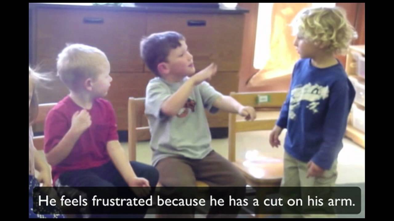 """A video frozen in a scene that shows three young children signing to each other. The subtitle on the screen says """"He feels frustrated because he has a cut on his arm"""""""