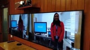 "Two large television screens side by side show a woman standing next to a computer screen with the word ""HELLO"" printed on it in large letters."