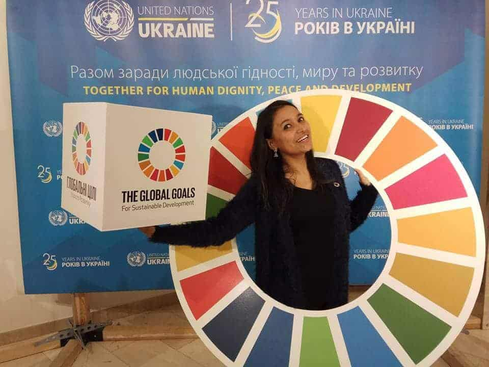 """A woman stands inside a large circle with 17 colors, each representing one of the 17 Sustainable Development Goals (SDGs). She also holds a box with the same SDG logo and the slogan """"The Global Goals for Sustainable Development""""."""