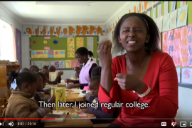 Screenshot from a video documentary on Kenyan deaf professionals. Shows a woman signing to the screen while school children are working at desks behind her.