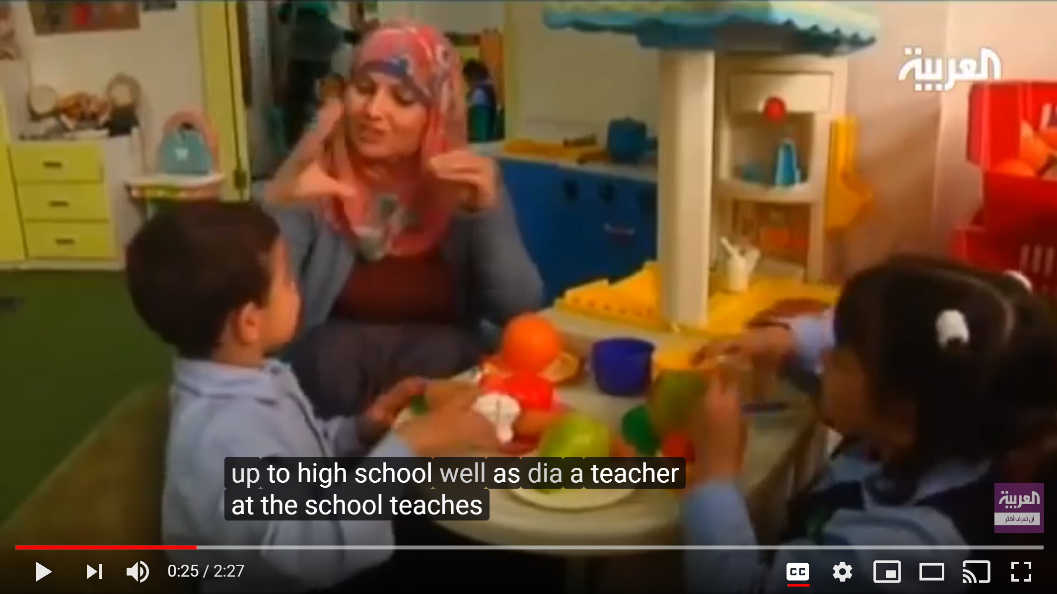 Screenshot from a video on the Atfaluna Society for Deaf Children. A teacher and two young students are seated around a table signing to each other.