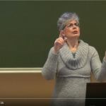 Screenshot of a video that shows woman presenting in sign language on deaf women's rights and health.