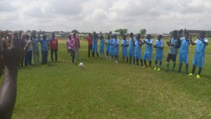 One long row of soccer players pose for the camera while standing on an open field. One soccer ball is on the ground near the center of them. To the right, everyone is dressed in blue. To the left, people are dressed in different colors.