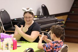 """An adult and a child are seated together at a table. The adult is wearing bunny ears. She teaches the child the sign for """"bunny""""."""