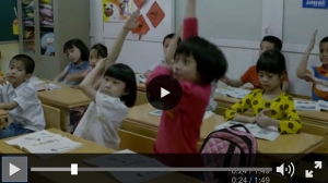 This screenshot shows a video frozen in a scene that shows children in a classroom. Some of the children are raising their hand with enthusiasm.
